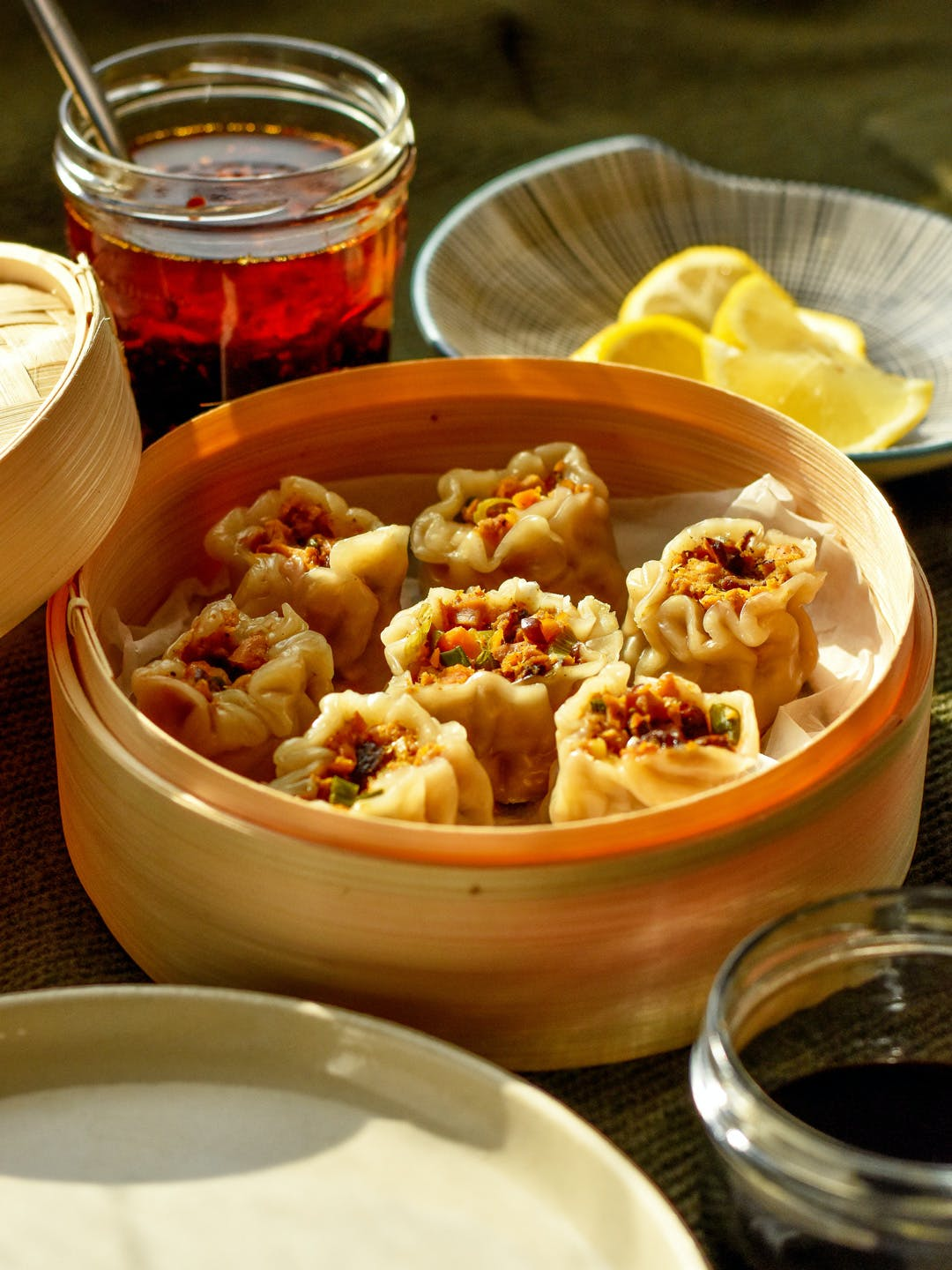 vegan filipino siomai in a bamboo steamer served with garlic chilli oil, lemon wedges and soy sauce