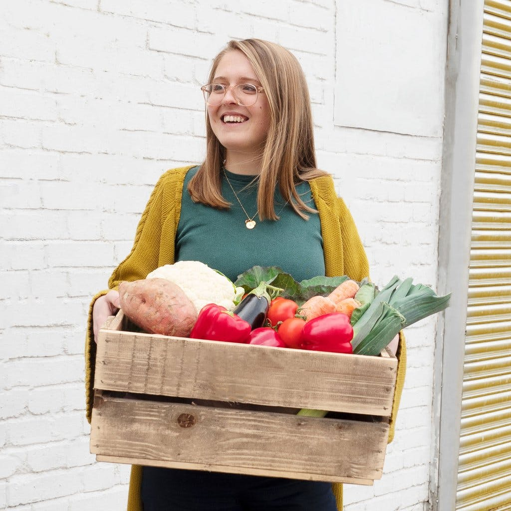 Image of Ellie holding a wooden crate full of red peppers, leeks, and cauliflower, stood in front of a white brick wall. She's wearing a green t-shirt and mustard cardigan, and is smiling and looking to the left away from the camera.