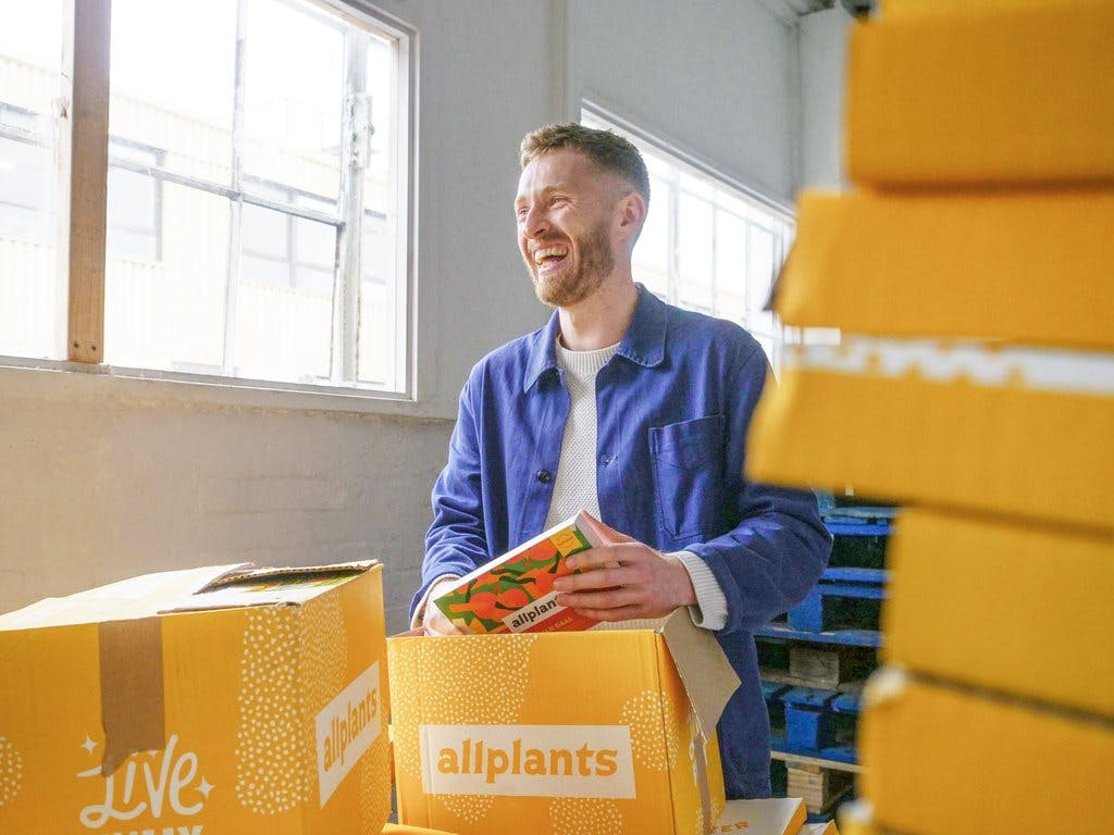Image of ferdie behind a couple of stacks of allplants delivery boxes. He's wearing a white t-shirt with an unbuttoned blue shirt layered over the top. He's smiling, looking away from the camera to the left and is packing an allplants dish into an open allplants delivery box.