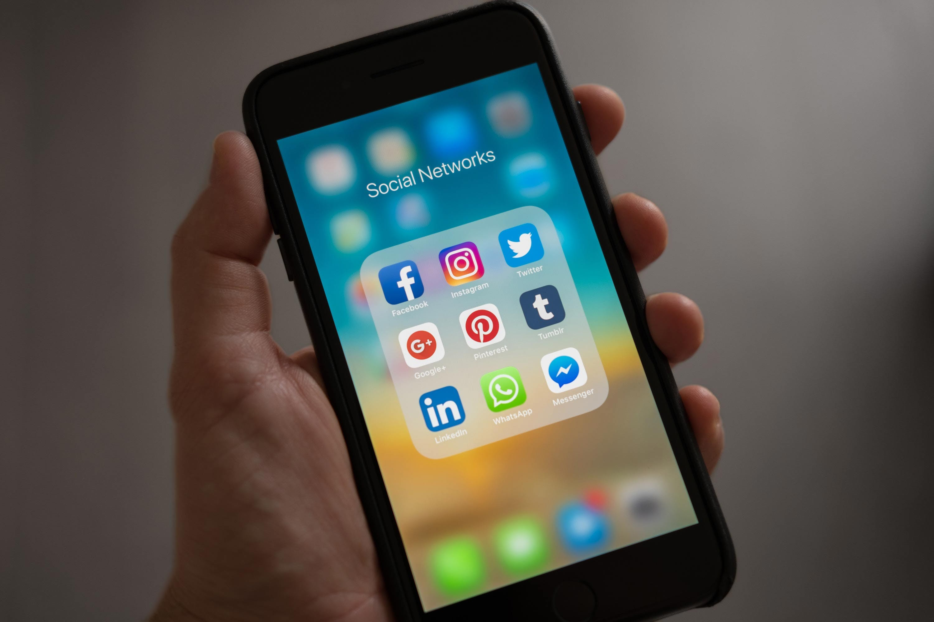 iphone in hand with social network apps