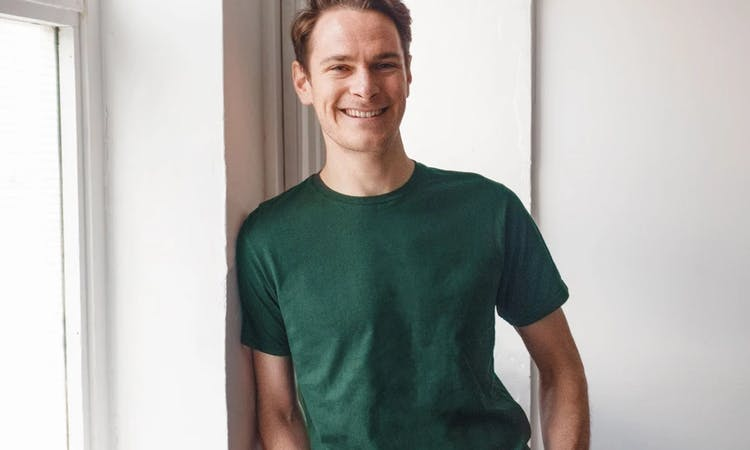 image of our engineering team lead, Barney. Wearing a green t-shirt, grinning, with his hands in his pockets, and leant against a window.