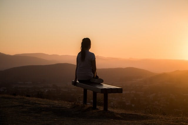 someone on a bench at sunset