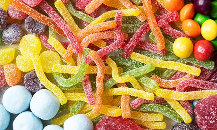 Close up image of sweets layed on a surface. There are fizzy worms in the middle, skittles in the top right, bonbons in the bottom left, jelly fruits in the bottom right, and fizzy jelly fangs in the top left.