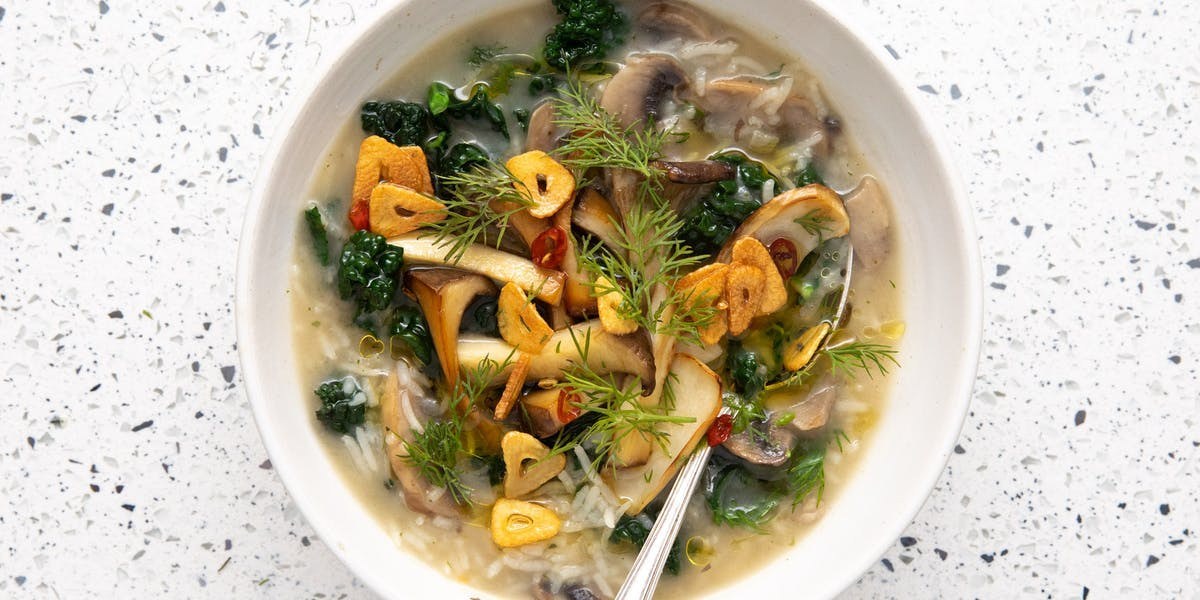 mushroom, rice and kale soup in white bowl with spoon