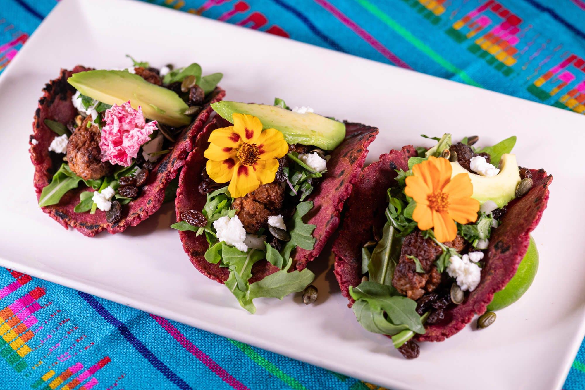 three vegan tacos on white plate