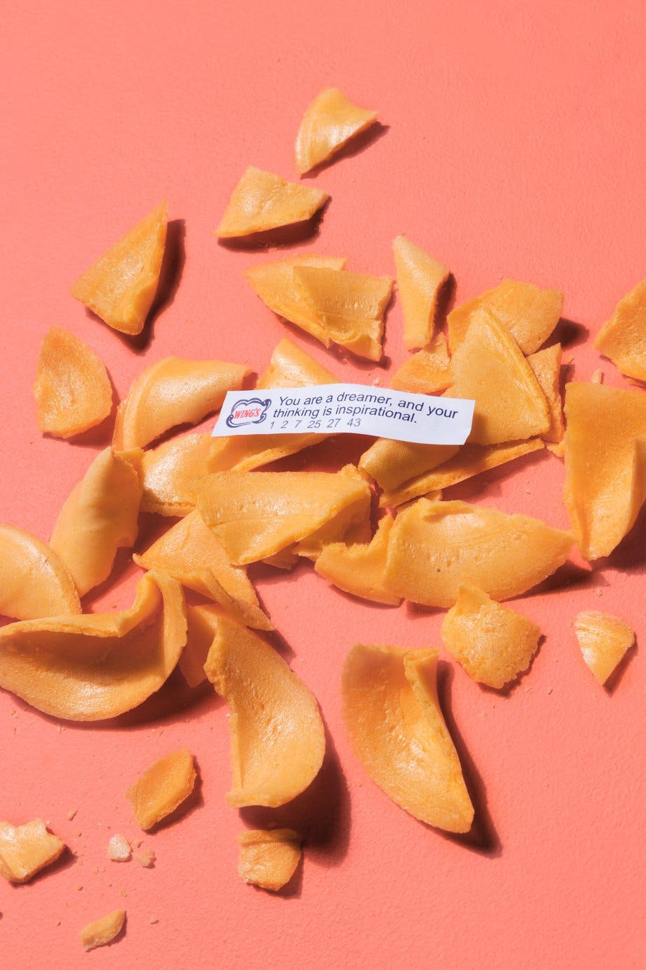 fortune cookies smashed on pink background