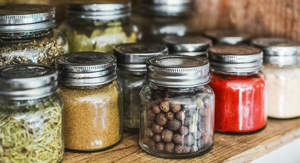 Herbs and spices stored in organised sealed jars