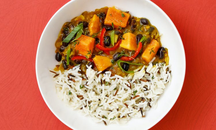 Sweet potato black bean curry in white bowl and red background