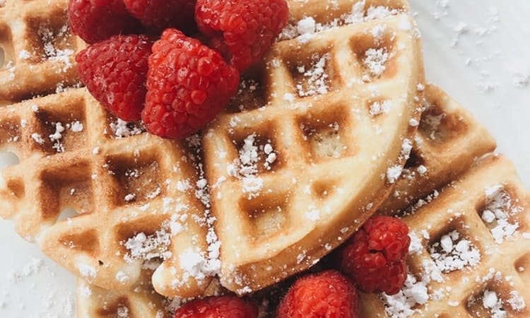 waffles with raspberries on top on a plate