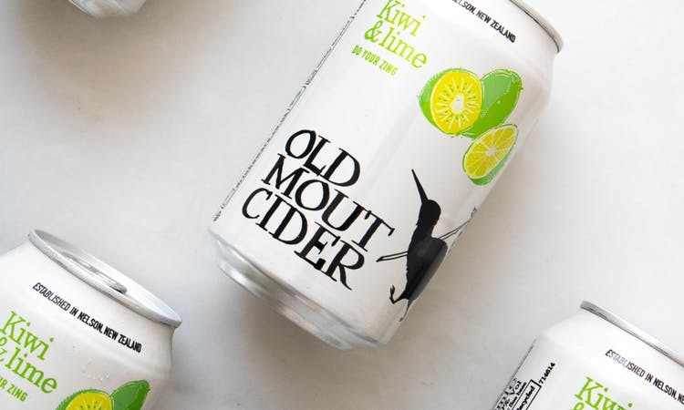 Image of cans of Old Mout cider, kiwi and lime flavour. Layed on a white table.