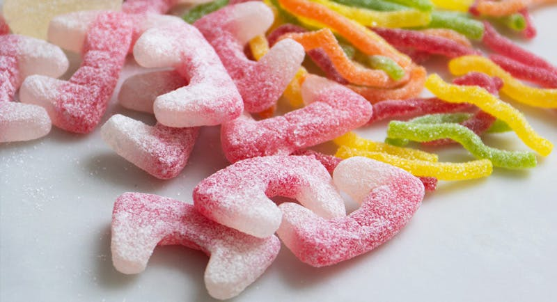 Close up image of sweets on a table, in front are fizy jelly fangs and there are fizzy worms in the background.