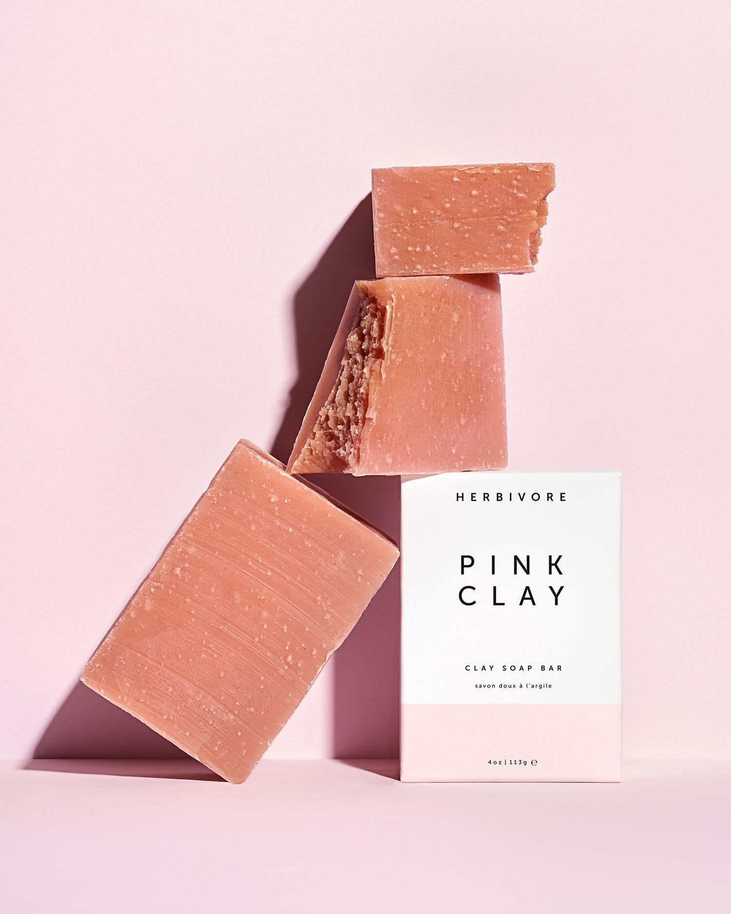 block of pink clay soap with box on pink background