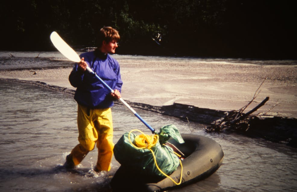 Scanned photograph of man in river with early packraft model and paddle