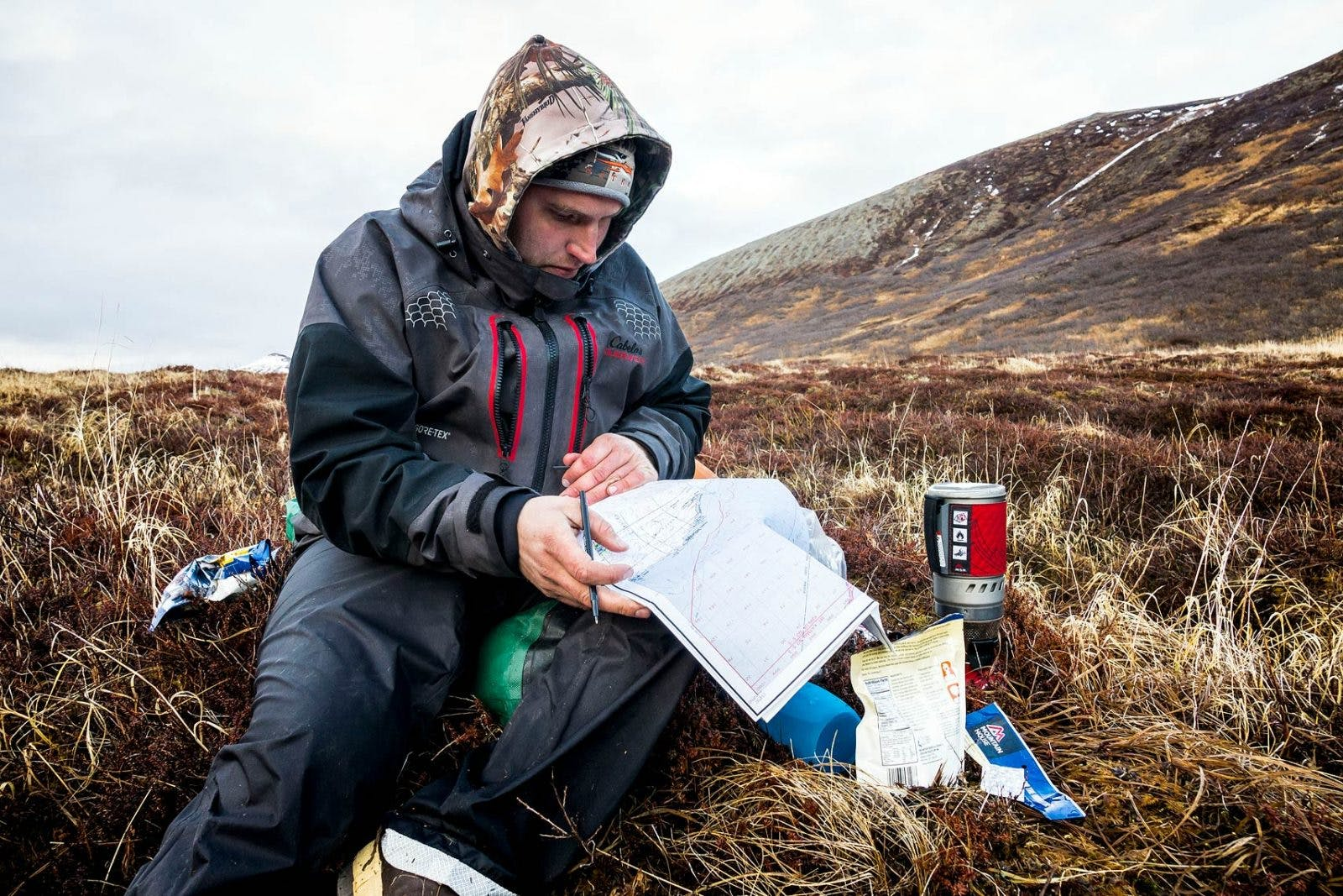 Bjorn Dihle reviews a topo map to plan the next day's route while boiling water for the evening meal.