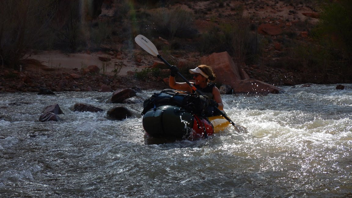"""""""With the many side hikes interrupting the paddling, we found ourselves on the water late into the afternoon with beautiful light. Here Sydney paddles through dappled sunlight peeking over the canyon walls that are several hundred feet above the water."""""""