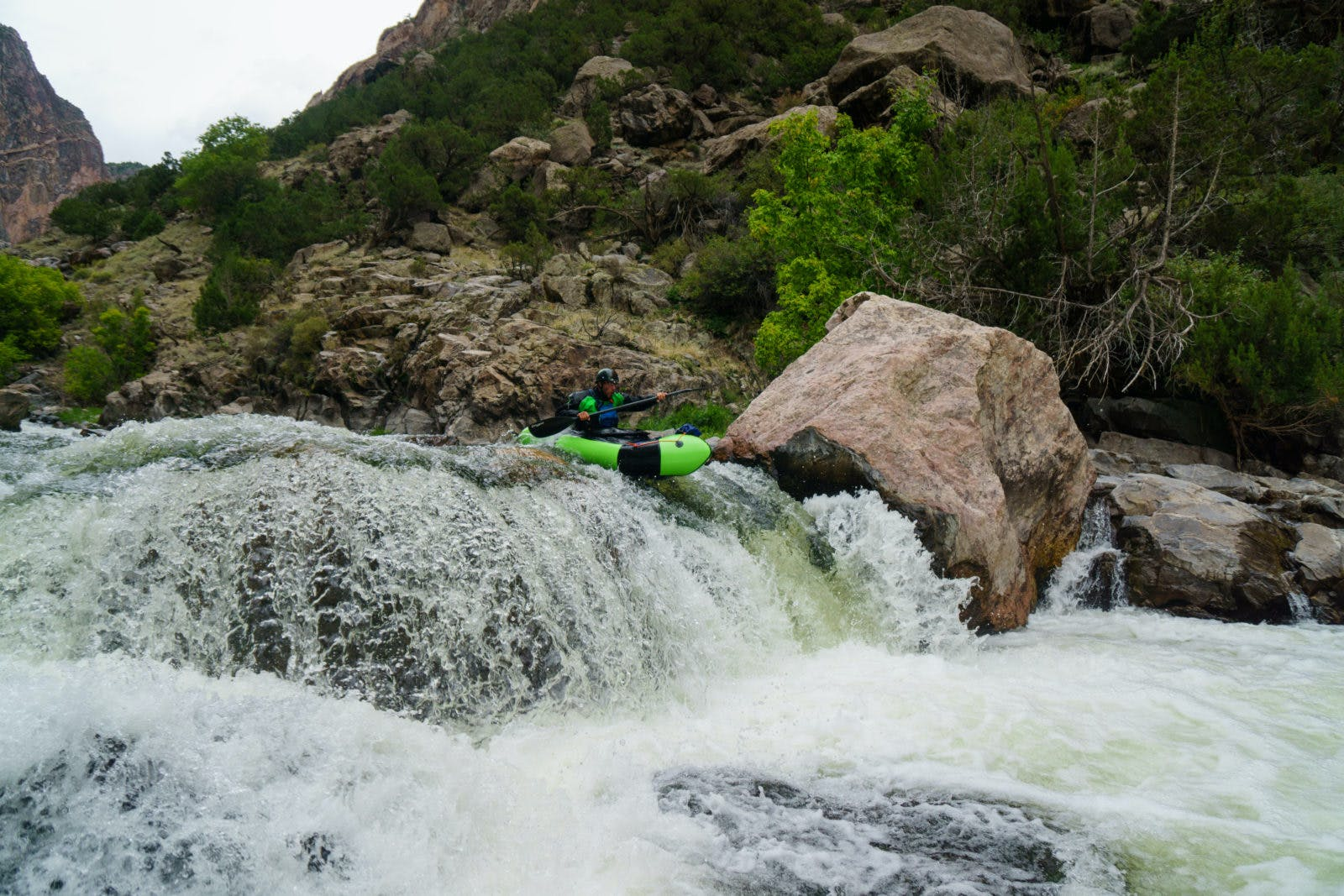 A lime green Gnarwhal launches off a waterfall in the Black Canyon. Photo by Thor Tingey.