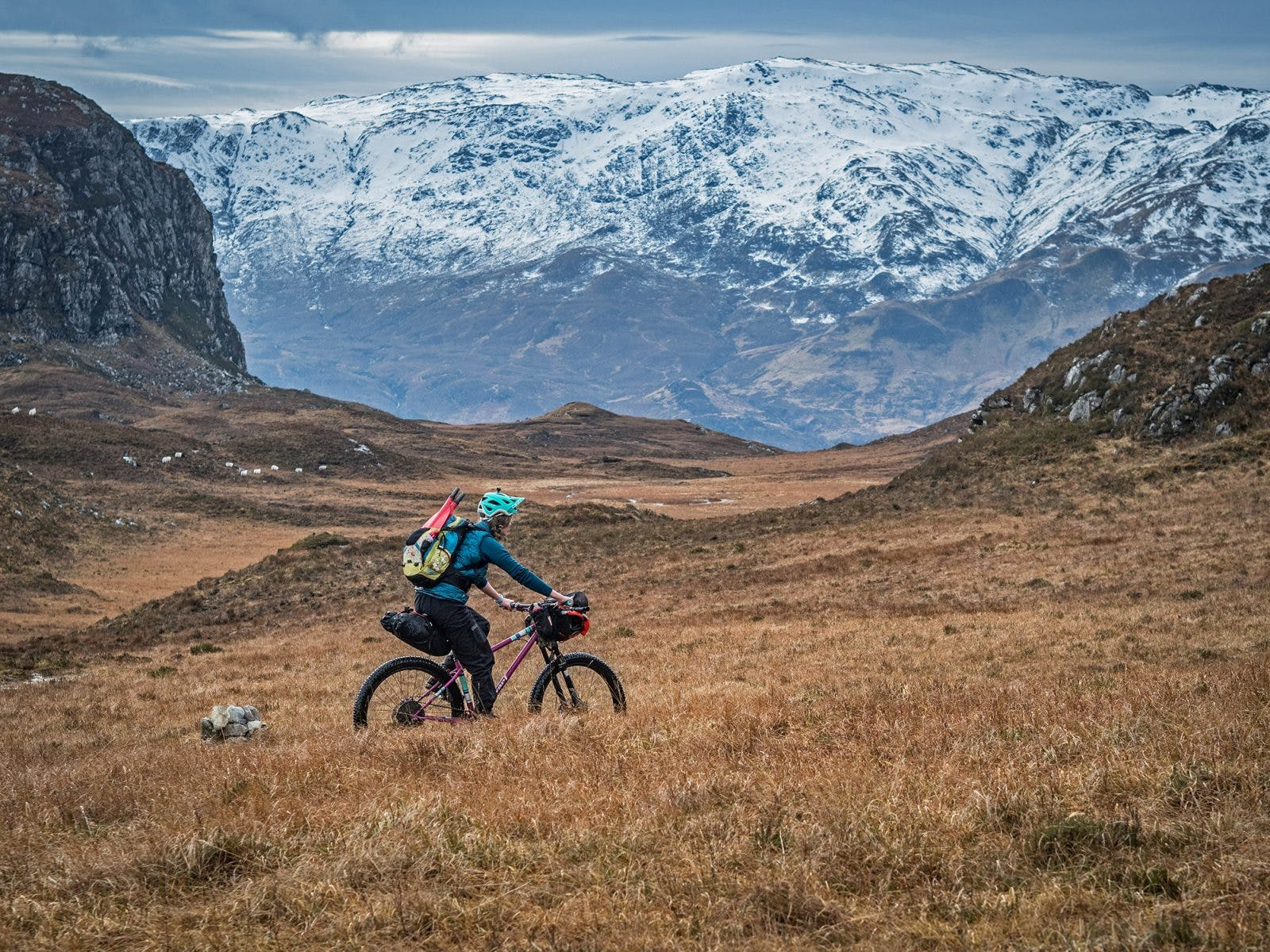 Annie Lloyd-Evans peddling across the Scottish Highlands with her raft rolled on the handlebars. Photo: Huw Oliver.