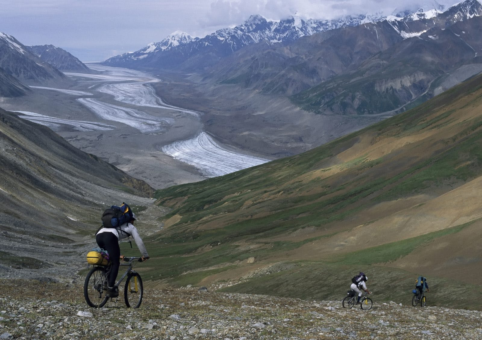 Expedition members descend a thousand feet toward the Black Rapids Glacier by bike. Photo by Bill Hatcher.Expedition members descend a thousand feet toward the Black Rapids Glacier by bike. Photo by Bill Hatcher.