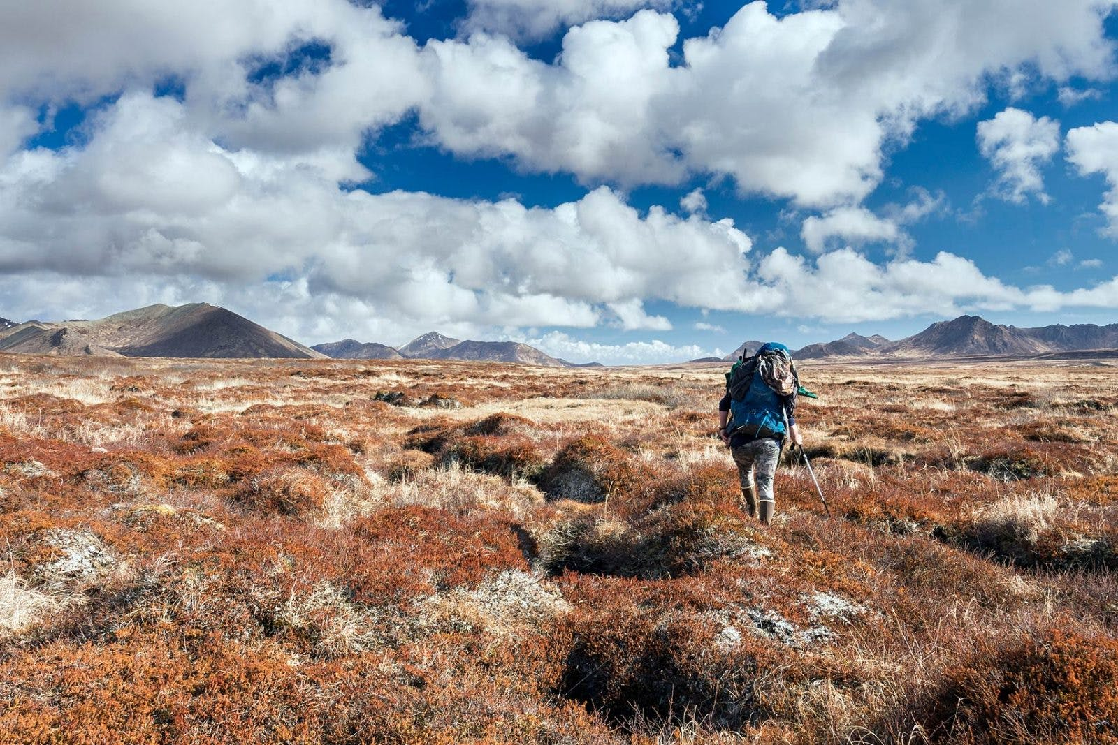 Bjorn Dihle traverses the tundra across a broad valley after 10-hours of hiking along the western edge of Kodiak Island near the convergence of Shelikof Strait and the Pacific Ocean. Dihle, a lifelong Alaskan, is an experienced trekker, bear guide, and writer.