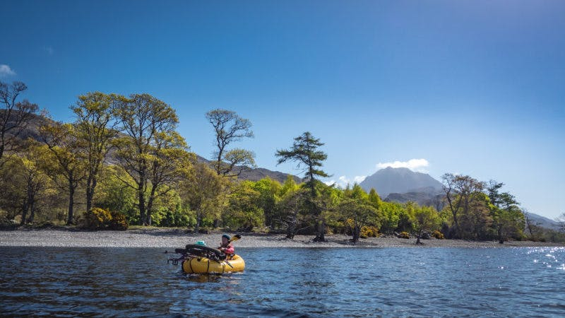 """""""Loch Maree in the north-west Highlands is home to some of the last remnants of Scotland's ancient Caledonian forest. In May we used rafts and bikes to access an otherwise fairly unreachable trail which runs underneath Slioch, the peak in the background behind Annie. It's a rarely visited trail, especially by bikes, and it ran amazingly well after a night spent bivvying at the top, and it eventually spat us out right down by the loch, where we hopped on the water to carry on our way in the sunshine."""" Photo: Huw Oliver"""