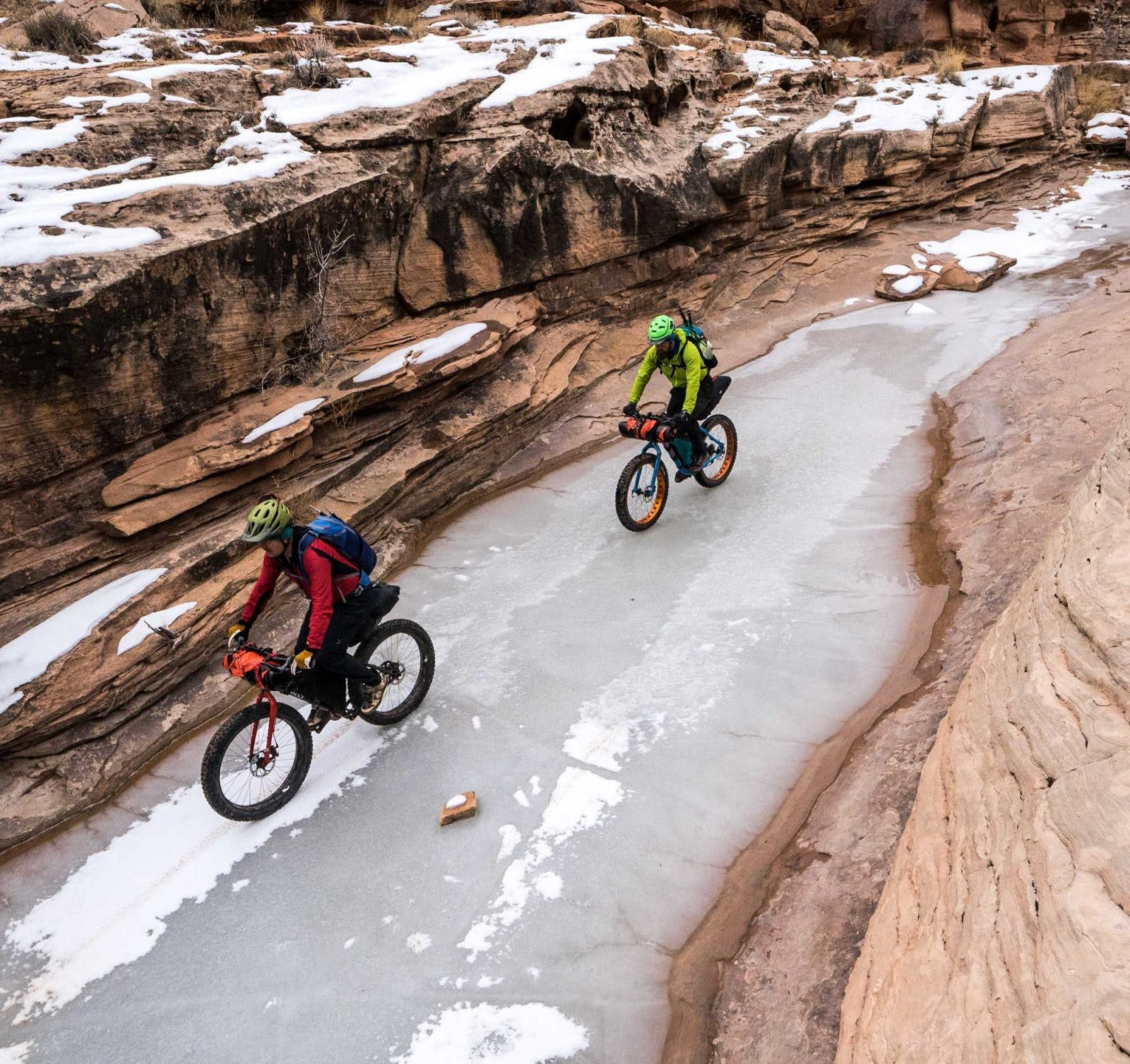 """Mike Curiak (in front) and CEO Thor Tingey riding ice en route to the Green River, with the new Caribou Packraft lashed to the handlebars. Photo by Steve """"Doom"""" Fassbinder."""