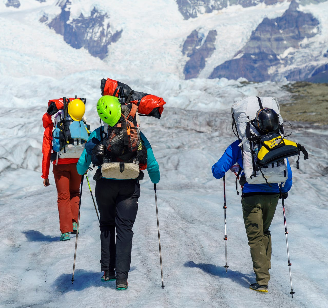 People hiking with packrafts over snowcovered landscape
