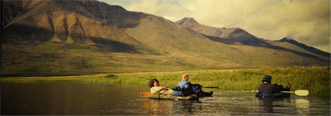 Scanned photograph of a group of people relaxing in water on packrafts with mountains in background