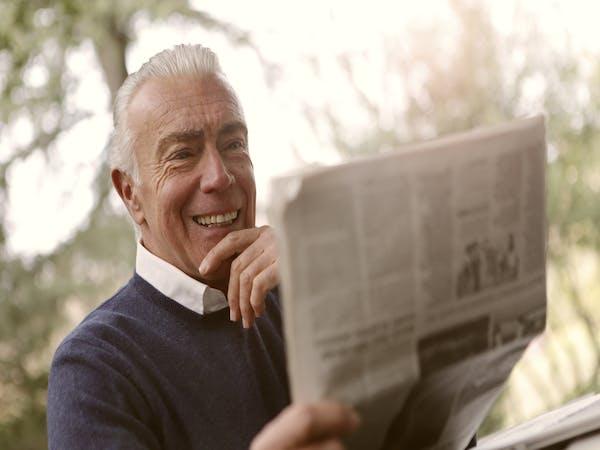 Homme retraité heureux de lire son journal paisiblement, sans se soucier de sa retraite car son PER (Plan Épargne Retraite) lui permet d'avoir un revenu complémentaire.