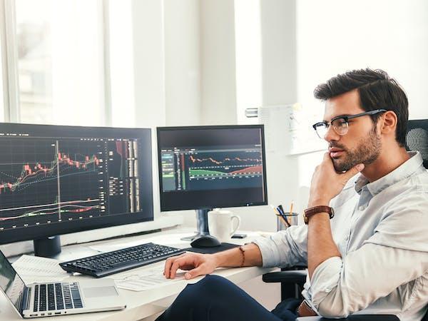 Investisseur financier observant sa rentabilité sur ses écrans, obtenue grâce aux professionnels d'Alphacap qui l'ont orienté vers les meilleurs fonds indiciel (ETF).