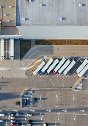 Entrepôt vu du haut avec l'arrivée de camions transportant de la marchandise. Ces locaux d'activité sont acquis par des investisseurs via des SCPI (Sociétés Civiles de Placement Immobilier).