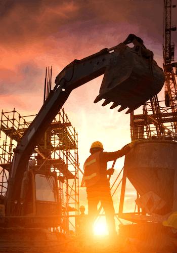 Chantier de construction d'un actif immobilier, sur lequel on peut voir un ouvrier et un engin de chantier au coucher du soleil.