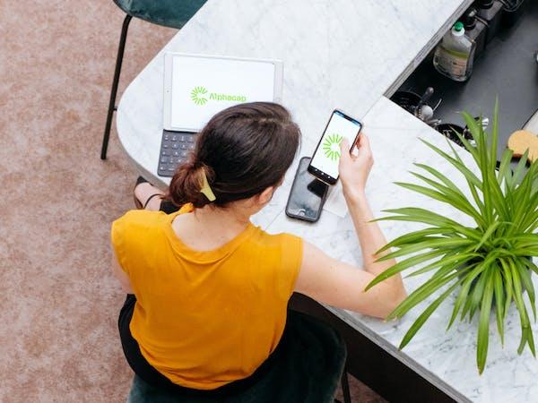 Femme sur son téléphone et sur son ordinateur en train de consulter les différentes plateformes d'Alphacap afin d'accompagner ses clients et de garder la main sur son fichier.