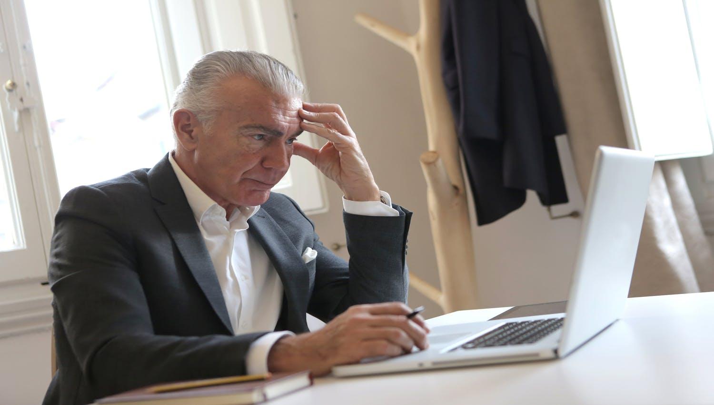 Homme en costume s'énervant devant son ordinateur en cherchant comment réduire ses impôts car il ne connait pas Alphacap pour avoir des conseils de la part de professionnels concernant ses placements.