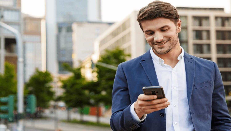 Jeune homme heureux de pouvoir suivre ses placements et la construction de son patrimoine en temps réel depuis son téléphone.