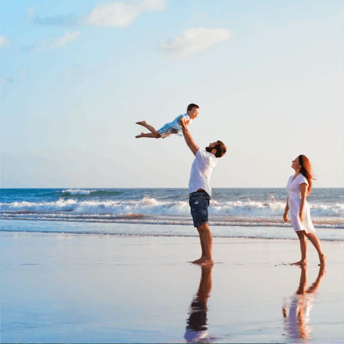 Famille heureuse sur la plage, qui a pu s'offrir des vacances grâce à des placements financiers intelligents et a pu percevoir des revenus complémentaires.