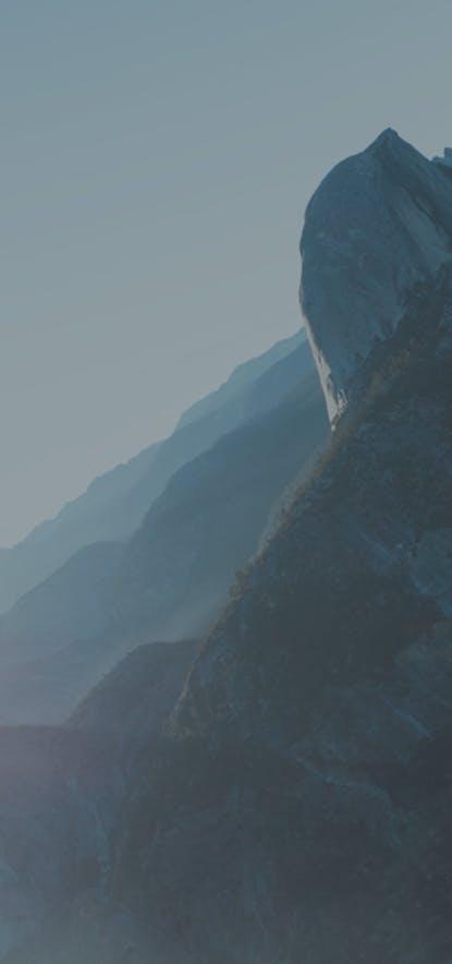 Homme debout sur une pierre, qui regarde l'horizon et l'avenir et qui réfléchit à répondre à une des offres d'emploi d'Alphacap.