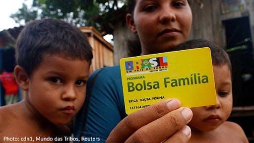 Woman holding Bolsa Familia card