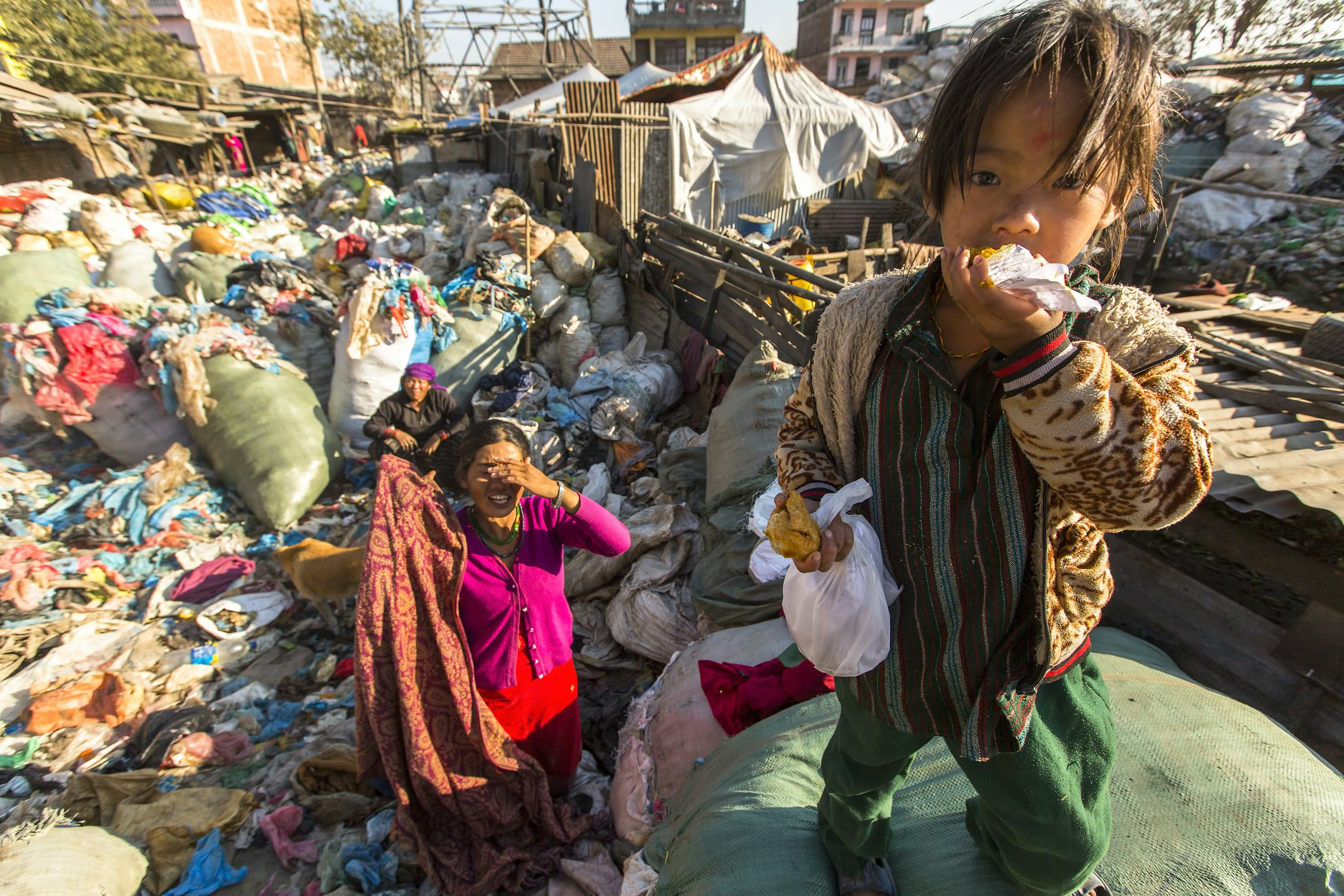 Child living in extreme poverty eating a morsel in a heavily-polluted town