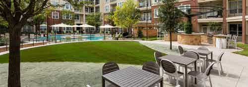 Daytime view of table and chairs near grill station at AMLI Frisco Crossing apartments with pool area in background