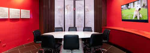 AMLI Uptown conference room with round white table table with eight black leather chairs and red walls and large window