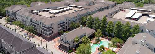 Daytime aerial view of AMLI Memorial Heights apartment buildings with view of curved pool and clubhouse in right foreground