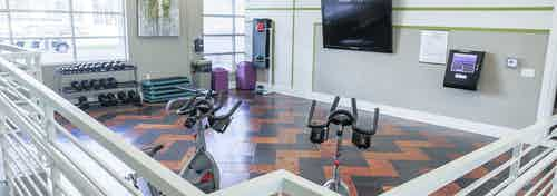 Interior view of a fitness on demand room at AMLI Arista apartments with stationary bicycles and free weights and television