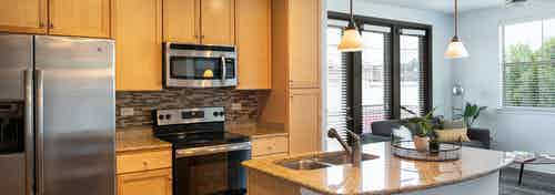 Daytime AMLI 300 apartment kitchen with an island, under mount deep stainless sink, and elegant granite counter tops