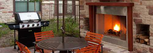 Daytime view of AMLI at Escena brick outdoor fireplace with brown table and four orange chairs and grill