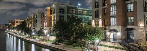 Nighttime exterior view of AMLI Las Colinas apartment building walkway along Lake Carolyn with trees and benches and lights