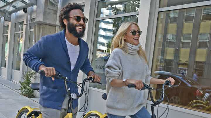 Man and woman wearing sunglasses and smiling while riding their bikes through town and stopping in front of a storefront