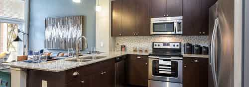 Interior of AMLI Frisco Crossing apartment kitchen with espresso cabinetry and tile backsplash and stainless steel appliances