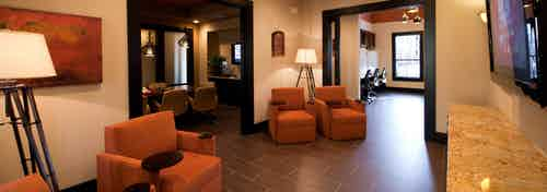 Interior view of resident lounge at AMLI at Escena apartment building with large orange chairs and big screen TV
