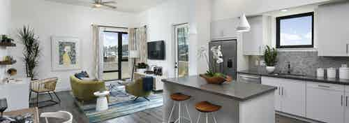Interior of AMLI Marina Del Rey furnished apartment kitchen with white cabinetry, gray quartz countertops and living room