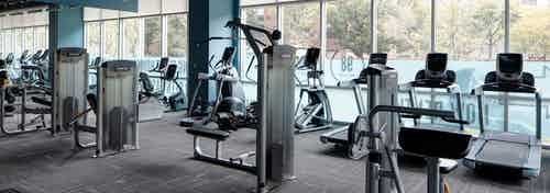 Interior view of the fitness center at AMLI Lofts featuring treadmills and elliptical machines as well as other equipment